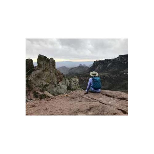 Person sitting on a rock overlooking a mountain scape