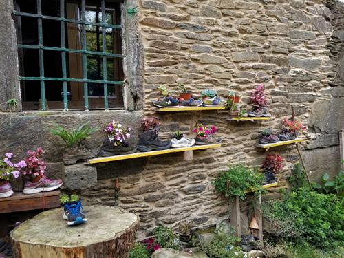Shelves on side of brick wall with plantings