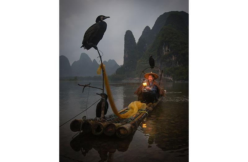 Photo of man on boat in darkness