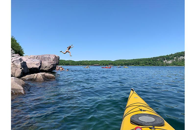 Photo of girl jumping into lake