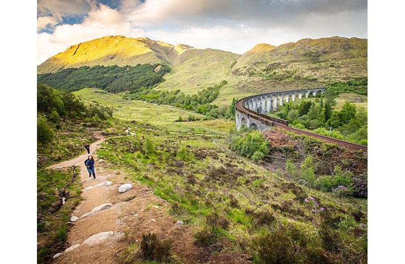 Photo of mountains with train bridge