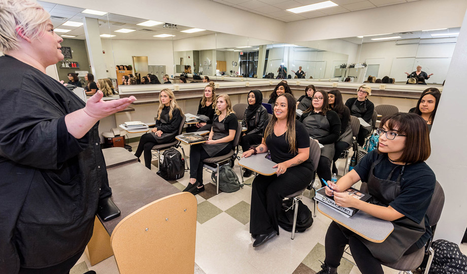 Instructor in front of room full of Cosmetology students