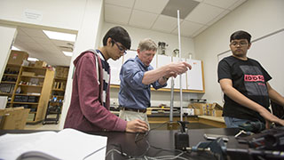 professor teaching two students about physics in a hands-on lab