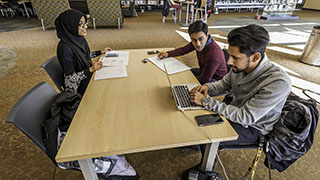 three students studying at a table in the cod library